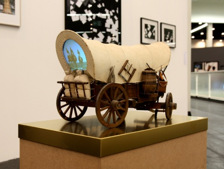 Own your share of business, 2010|Covered wagon (model) with projection|loop 8:36 min, pedestal, brassplate, DVD-Player, Mini-Beamer|65 x 40 x 100 cm